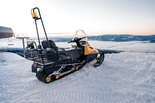 Snowmobile in the snow on the skiing hill of the ski area.ountai